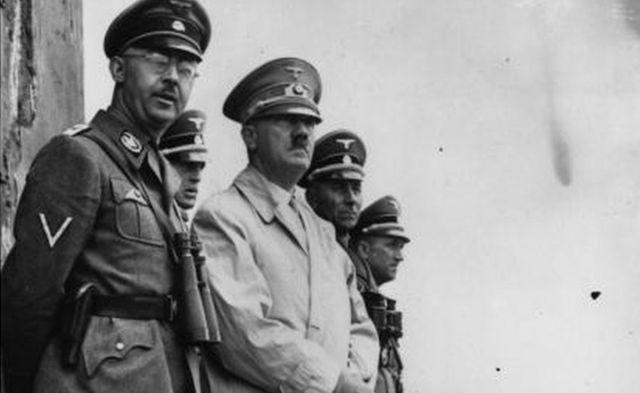 El dictador alemán Adolf Hitler y el líder nazi y jefe de la policía alemana Heinrich Himmler (izquierda) observando las maniobras de las tropas de asalto.